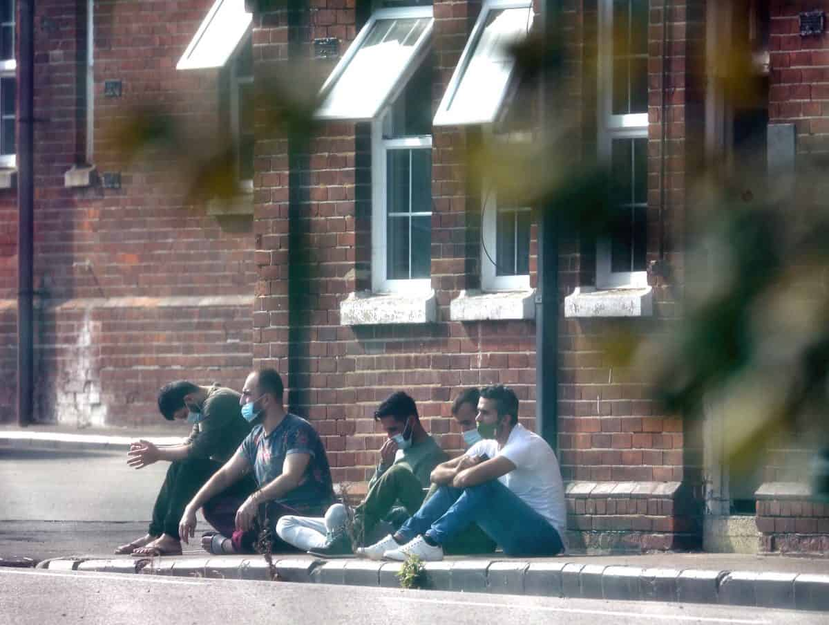 A group of men, thought to be migrants, sit outside in the sunshine after arriving yesterday night at Napier Barracks in Folkestone, Kent. Credit;PA