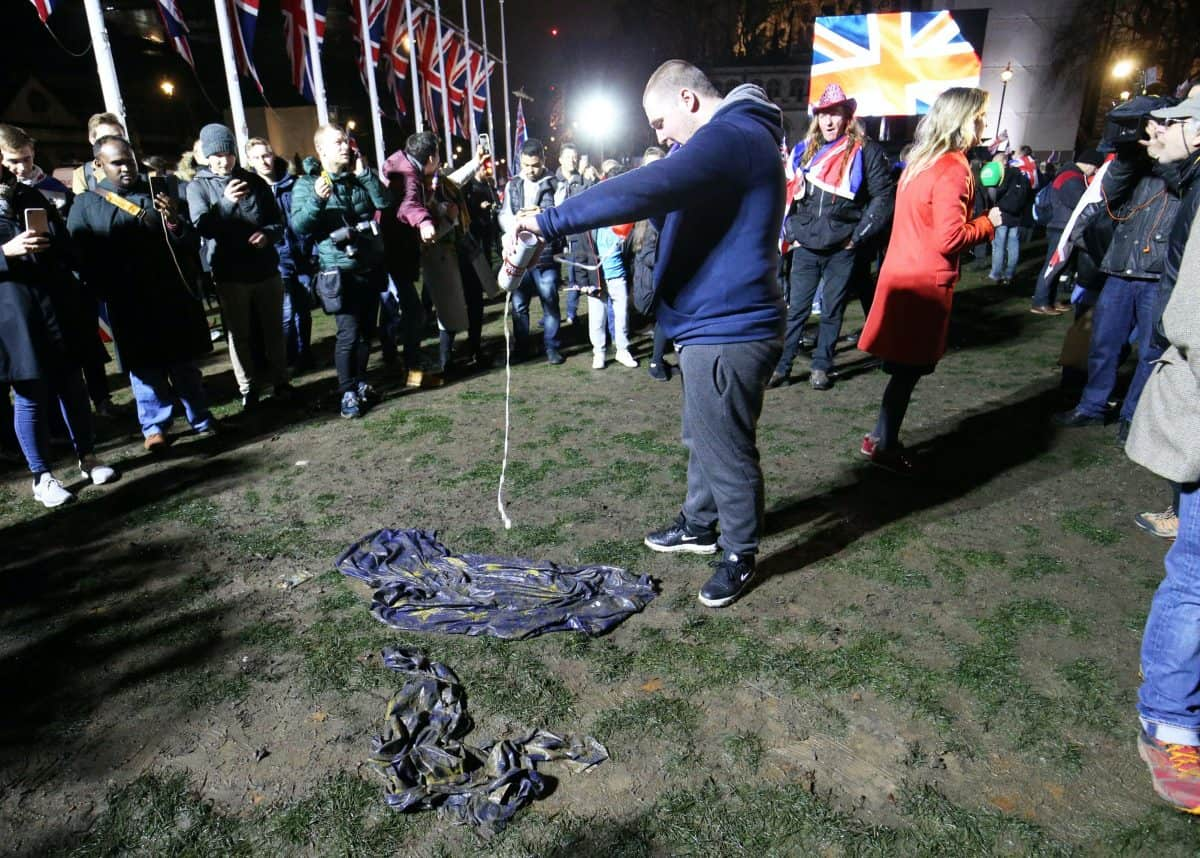 A pro-Brexit supporter pours beer onto an EU flag in Parliament Square (Jonathan Brady/PA)