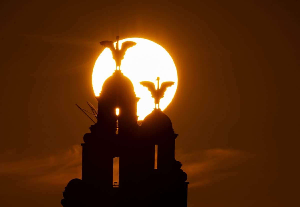 The sun rises behind the Royal Liver Building on Liverpool's waterfront, seen from across the river Mersey, ahead of the chance that Britain could bask in the hottest day of the year so far this week.