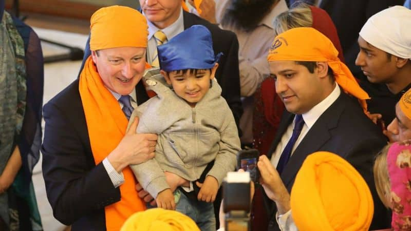 Samir Jassal (right) with David Cameron on a visit to a Sikh place of worship in Kent, 2015
