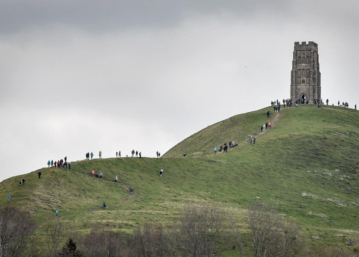 People walk up to St Michael's Tower on the top of Glastonbury Tor, Somerset, as forecasters have warned of treacherous driving conditions for Easter holidaymakers with snow and torrential rain on the way.