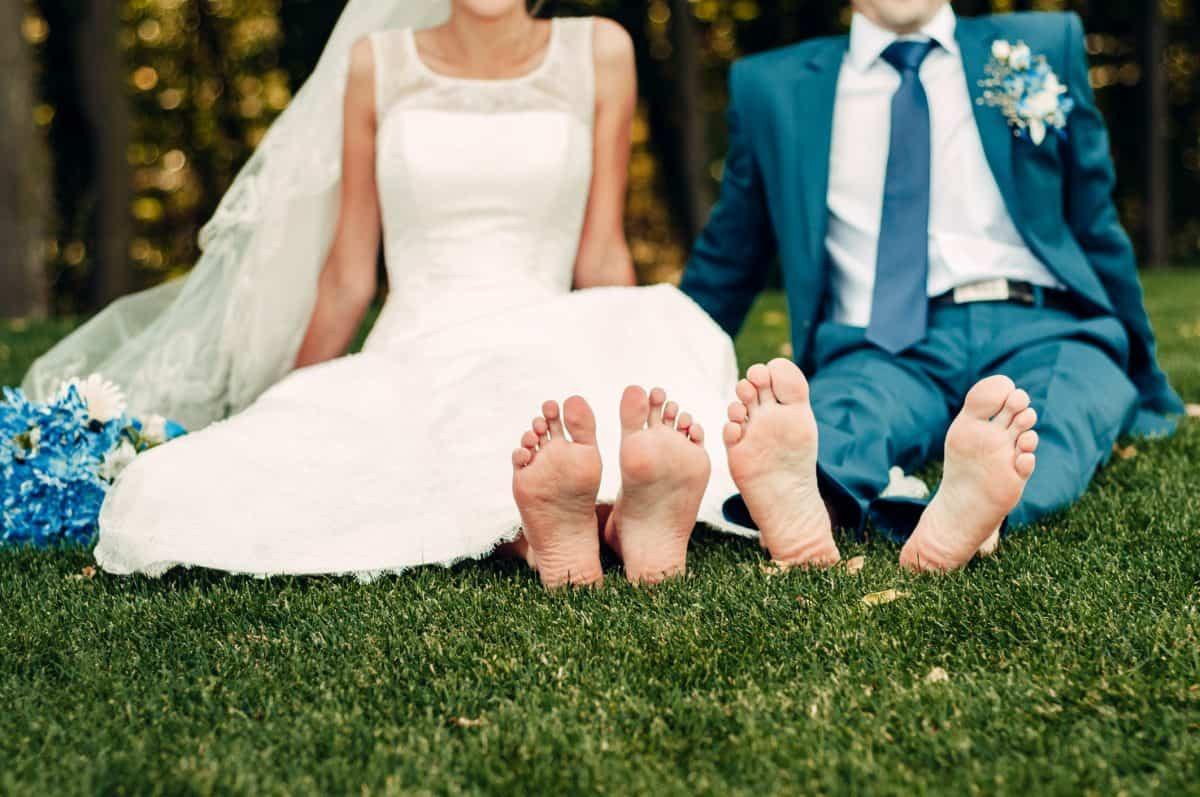 barefooted young fair-haired bride and her fiance sits on the grass in an exotic park, in a long white dress with a bouquet of flowers in her hands, a walk after the wedding ceremony, a wedding ceremony
