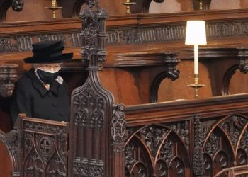 The Queen sitting alone whilst wearing a mask at her late husband Prince Philip's funeral. Photo: PA.