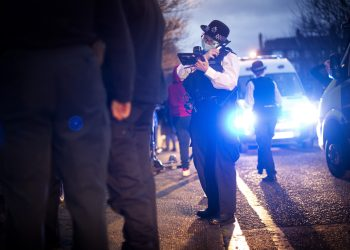 A female police officer uses her radio during a stop and search of a suspect in Walworth, Southwark during an all female operation by the Metropolitan Police, the first of its kind for the force, to mark International Women's Day. Picture date: Saturday March 6, 2021.