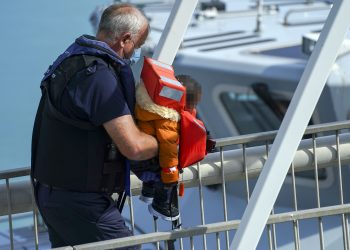 EDITORS NOTE Children's faces have been pixelated as the PA Picture Desk has been unable to gain the necessary permission to photograph a child under 16 on issues involving their welfare. A young child is carried ashore as a group of people thought to be migrants are brought in to Dover, Kent, by Border Force officers, following a small boat incident in the Channel. Picture date: Sunday August 15, 2021.