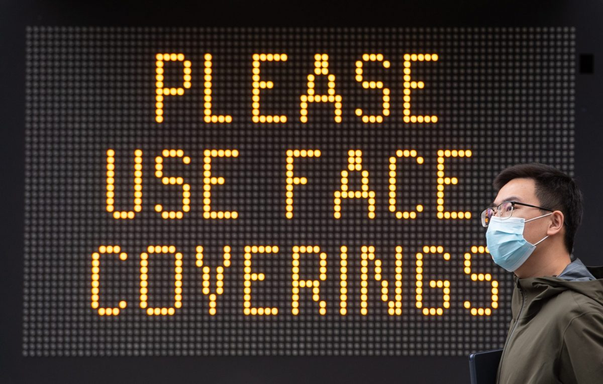 Embargoed to 0001 Thursday August 20 File photo dated 09/06/20 of a man wearing a protective face mask walking past signage advising the use of face coverings. Medical jargon surrounding masks may put some people off using face coverings, a new paper suggests.